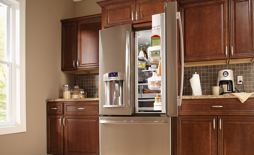 A built-in french door refrigerator with one of its doors open.