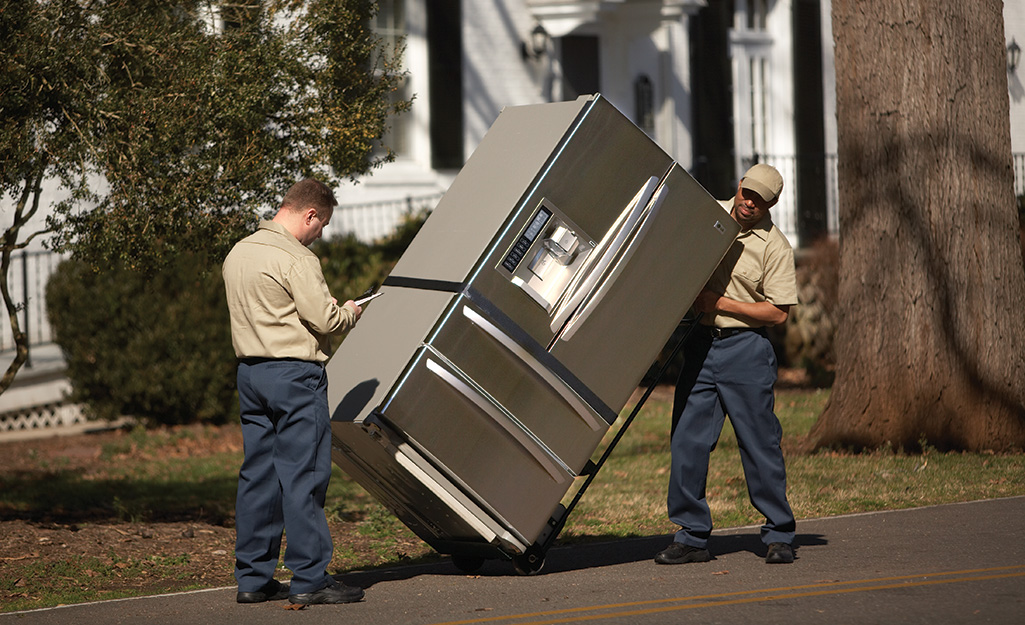 Two delivery men transporting a french door refrigerator on a dolly.