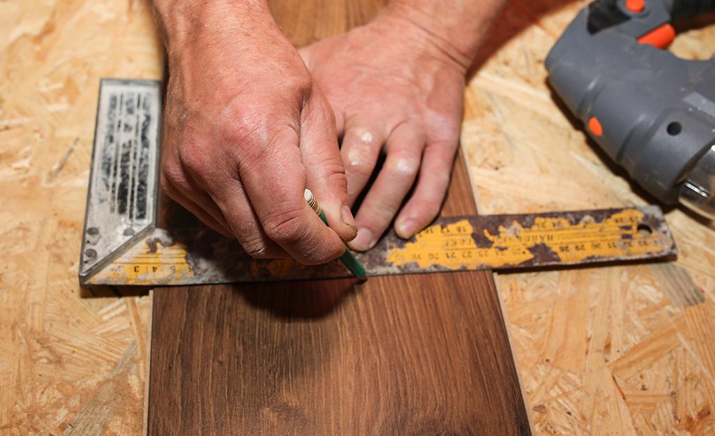 A person using a carpenter's square.