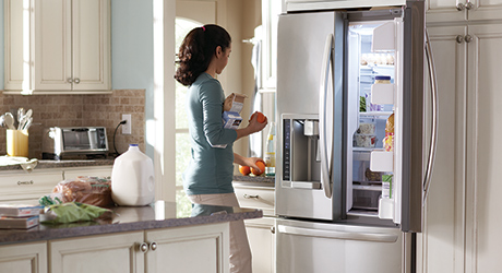 Woman standing in front of a French door refrigerator with an open door.
