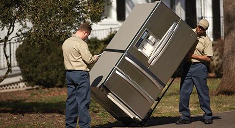 Two men delivering a refrigerator.