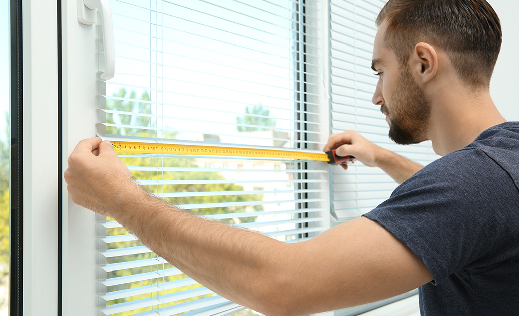 A man measuring a window for blinds.