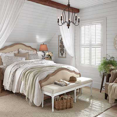 A bedroom with plantation shutters on the windows