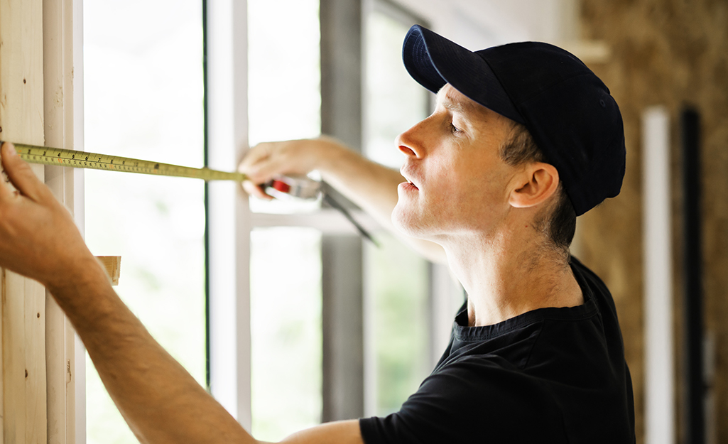 A man using a steel tape measure to measure the width of a window frame.