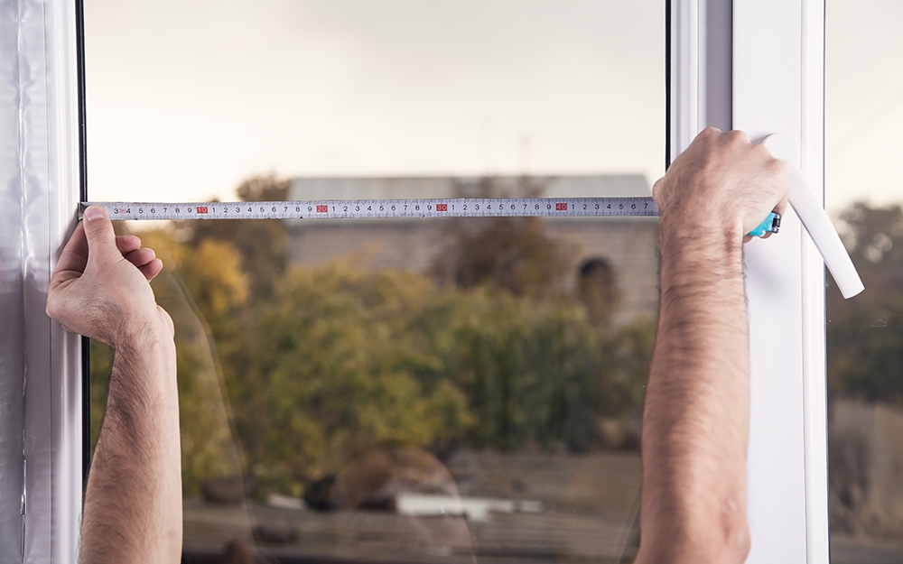 A person measures a window width.