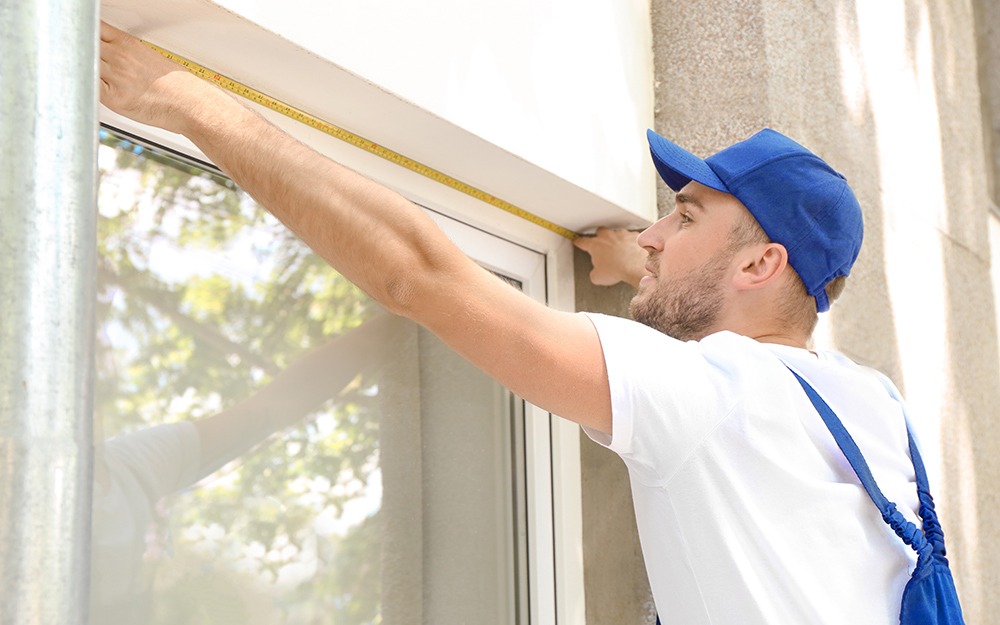 A person measures a window width using a tape measure.