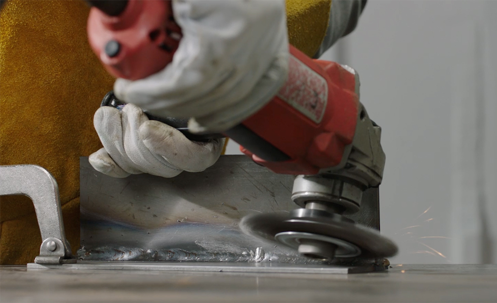 Someone grinding down a MIG weld bead using a grinder.
