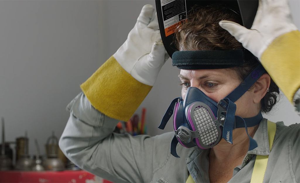 Someone geared up for MIG welding wears gloves, a respirator and a welding helmet.