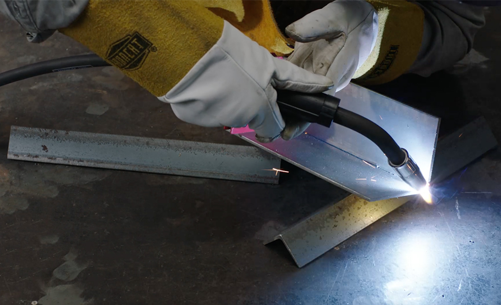 Someone starting a MIG weld on an inside corner of two metal pieces.