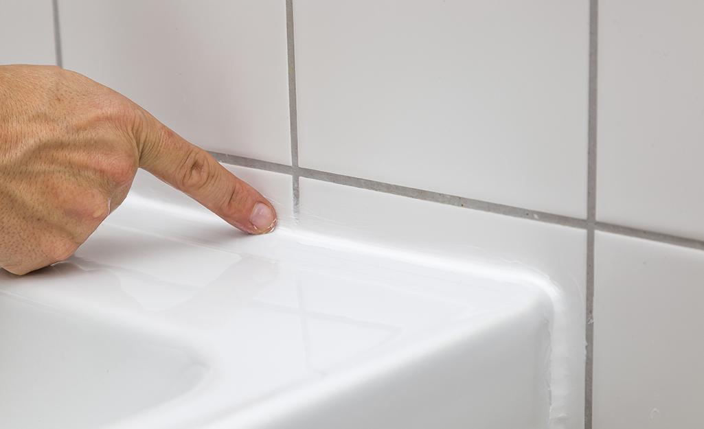 Một bàn tay đặt vào miếng đệm ở chỗ nối giữa bồn rửa và tường gạch.
