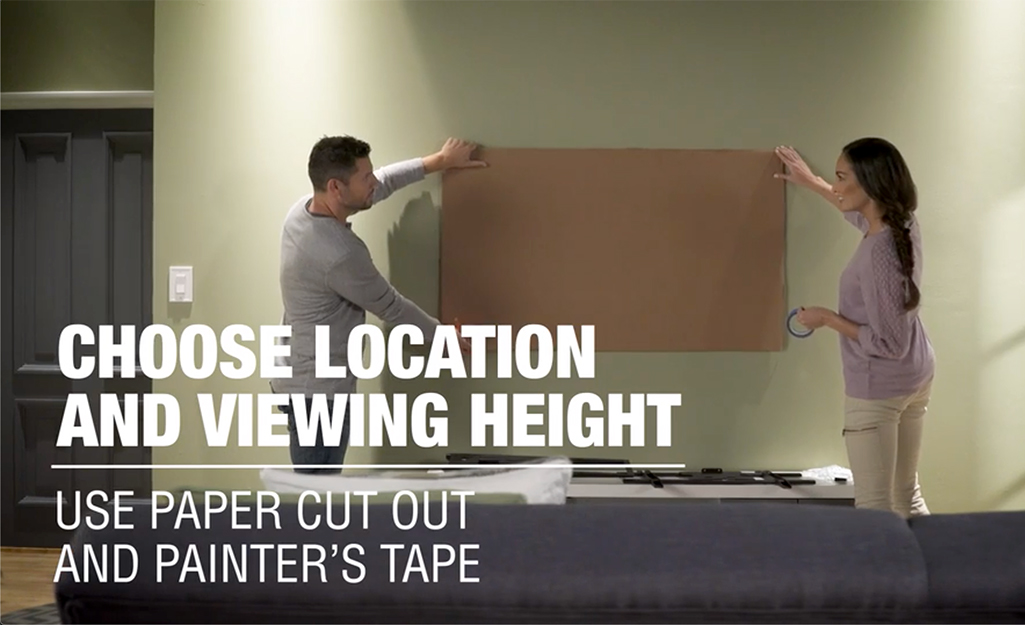 Hai người đánh dấu một chỗ trên tường để gắn TV.