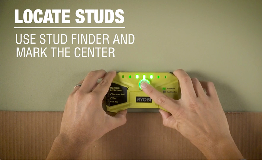 Person holding a stud finder against a wall.