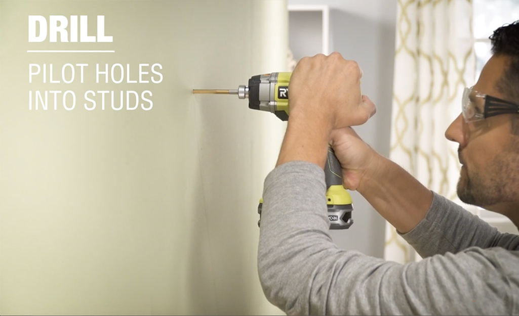 A person wearing safety goggles and drilling a hole in the wall with a power drill.