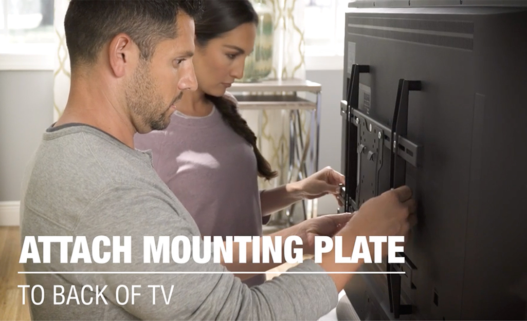 Two people attaching mounting plate to back of a TV.