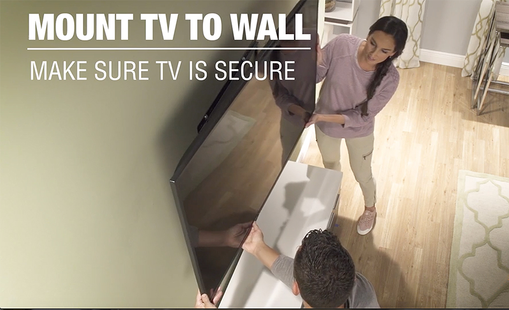 Two people mounting a TV to a wall.
