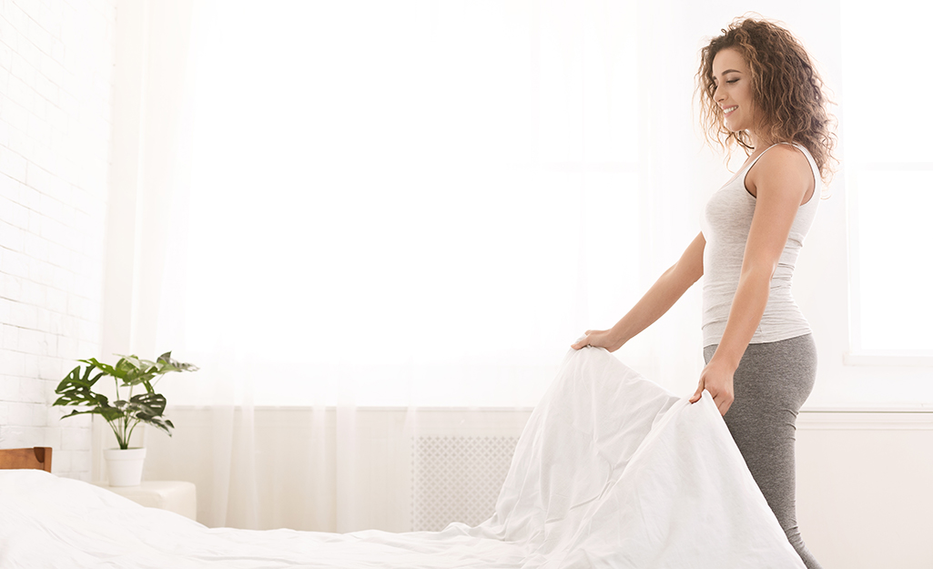 A person removing bed linens from a bed