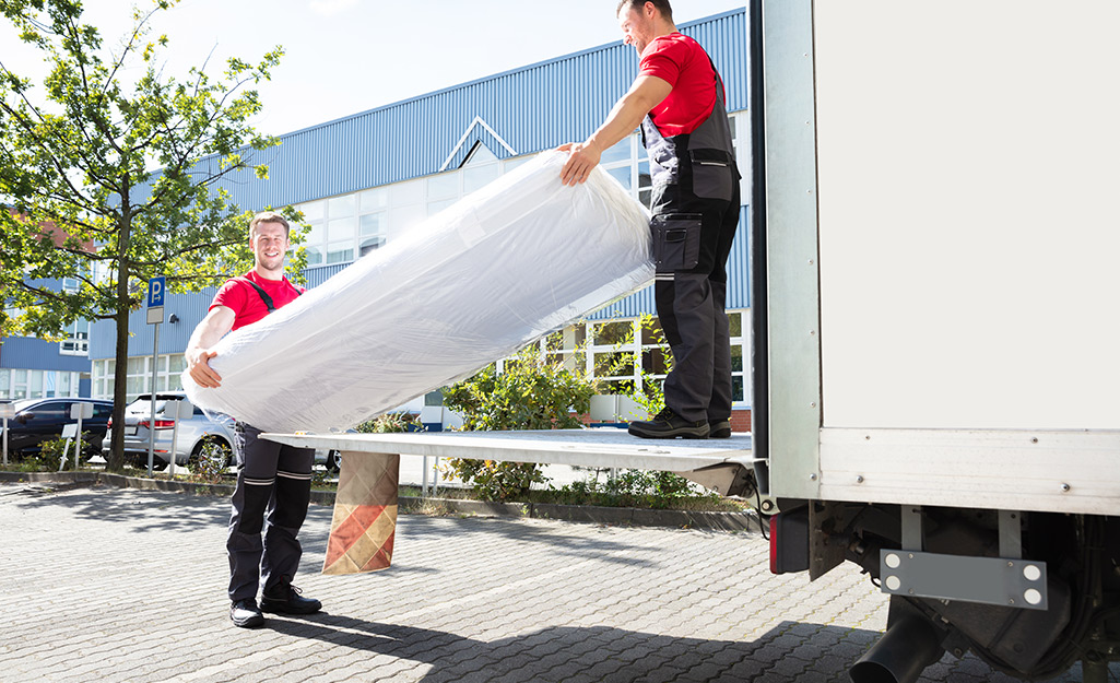Two people loading a mattress onto a moving truck