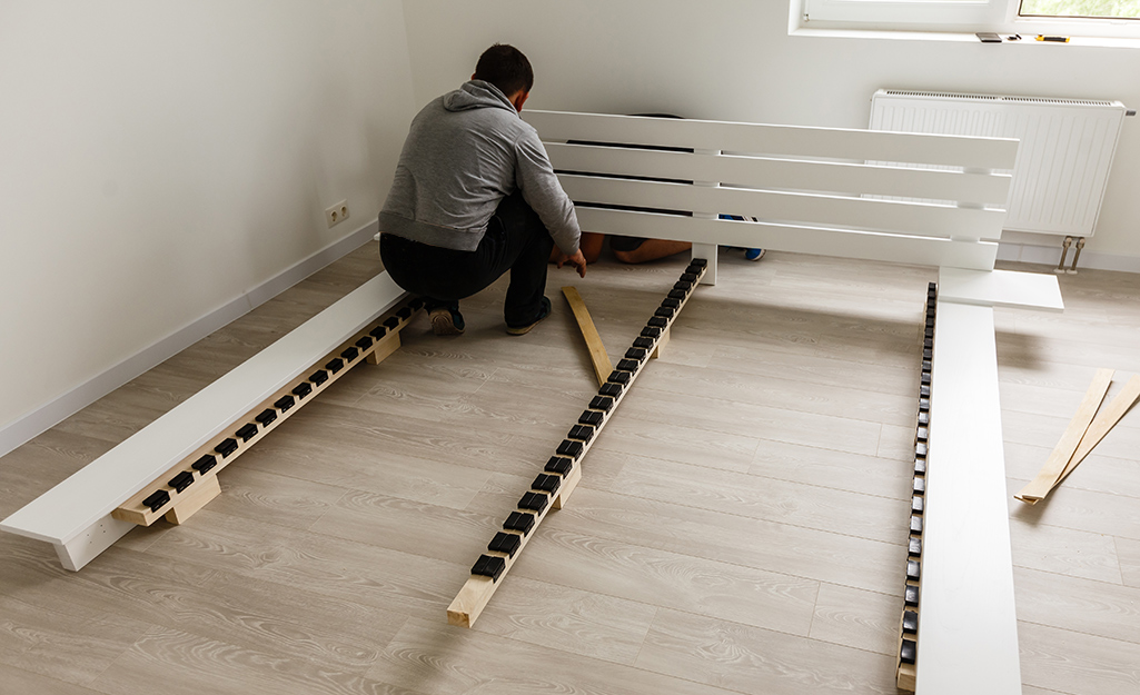 A person disassembling a bed frame