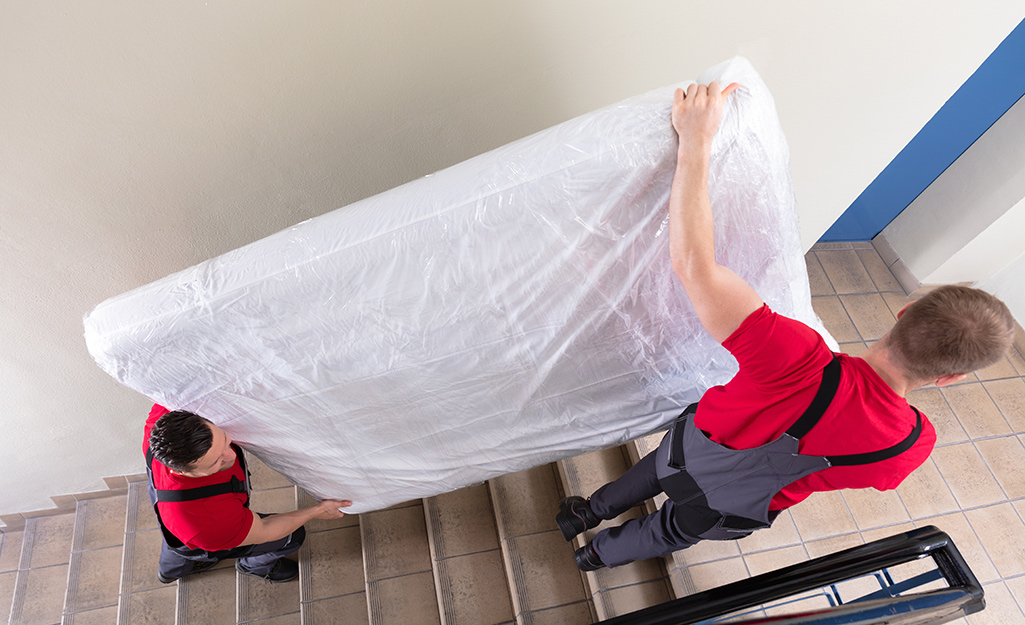 Two people moving a mattress into an upper floor of a home