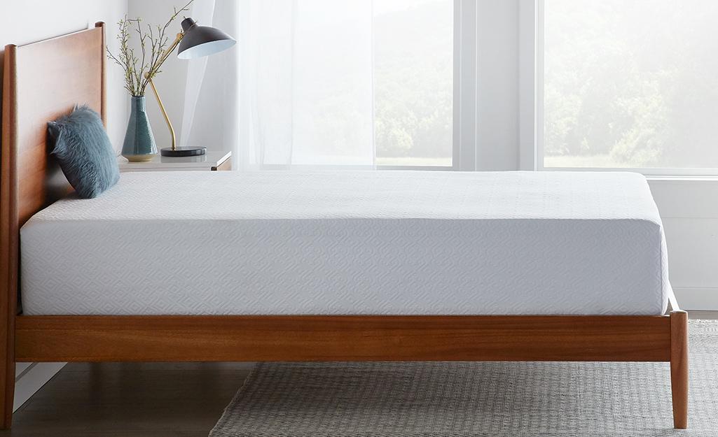 A memory foam mattress on a wood bed frame