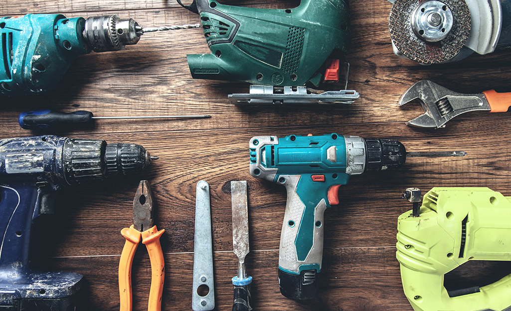 Drills, pliers and wrenches laid out on a wood table.