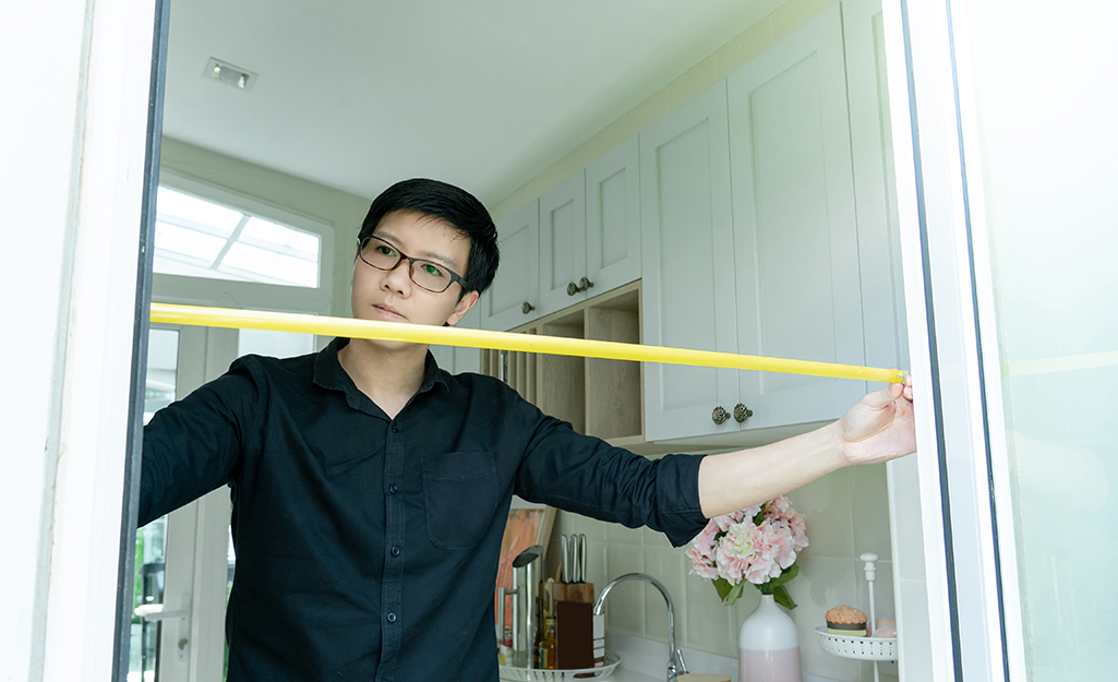 Man measuring a doorway with a yellow measuring tape.