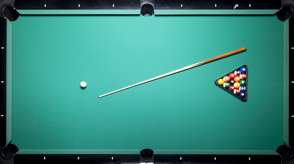Cue stick and a rack of pool balls lying on a pool table top.