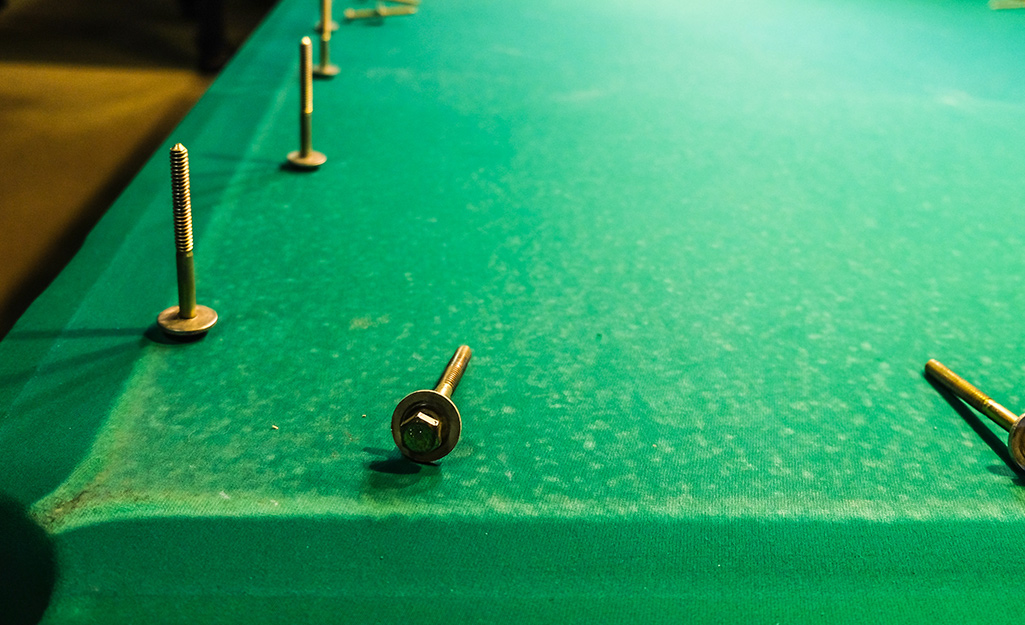 A pool table with unscrewed bolts placed on its felt.