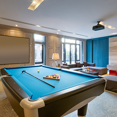 Pool table with blue felt placed in a modern den.