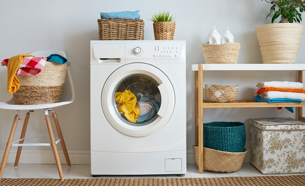 A washer sitting against a wall surrounded by baskets of clothes.