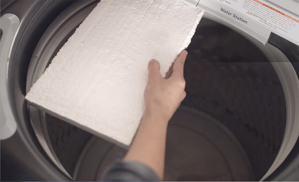 Someone placing foam core in a washer tub.