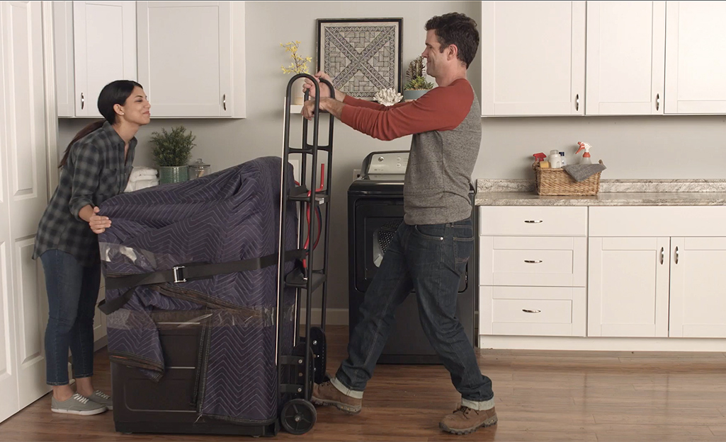 Couple placing wrapped washing machine onto a hand truck.