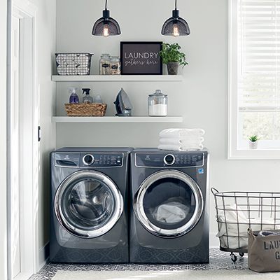 a sleek black washing machine and dryer sitting next to each other in a white laundry room