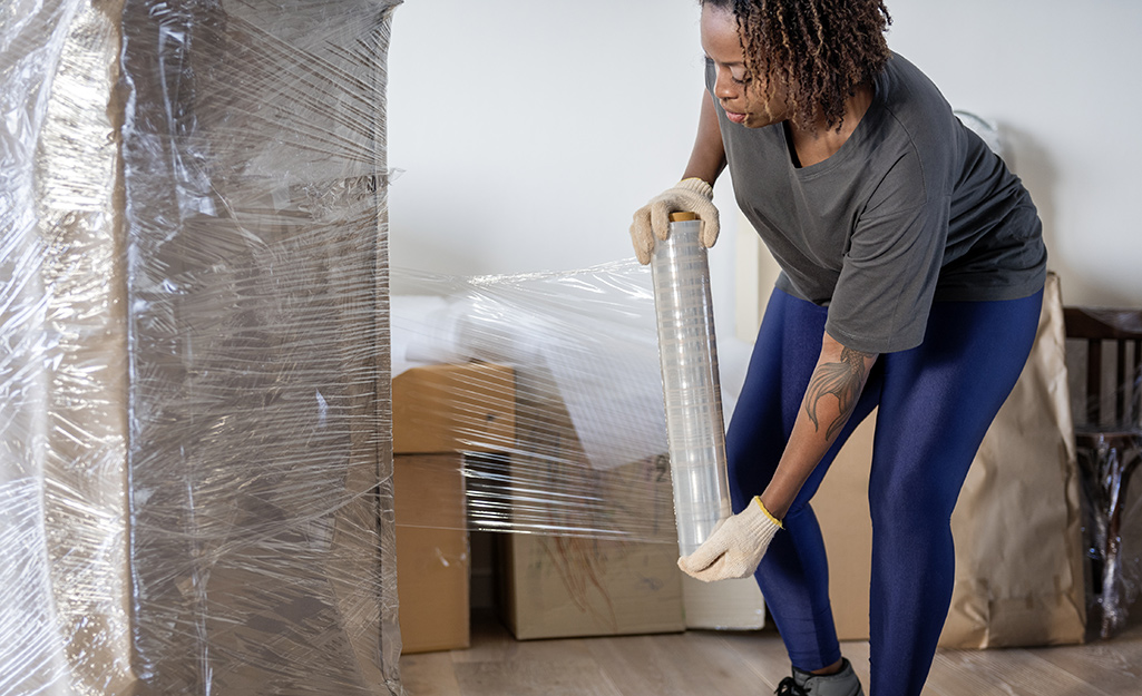 A woman uses stretch wrap to protect heavy furniture.