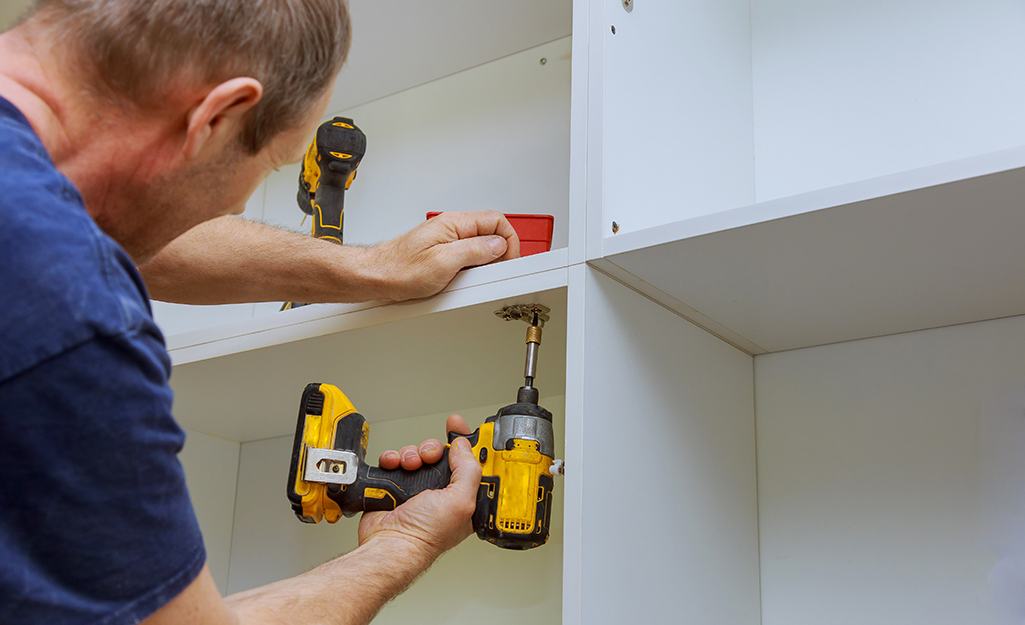A man uses a drill to disassemble furniture.