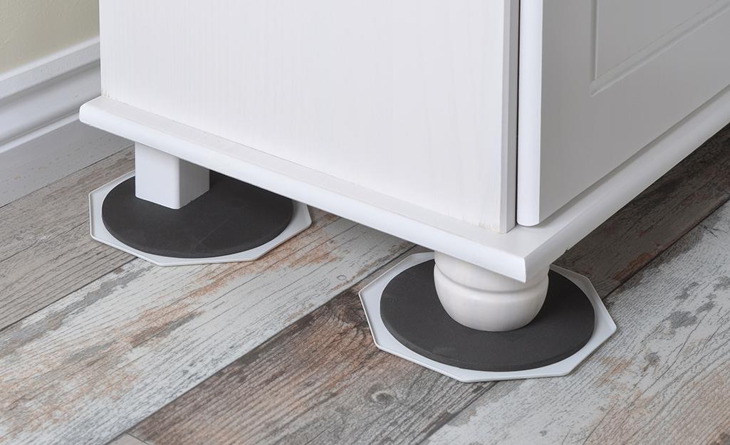 Furniture slides are placed under dresser legs.