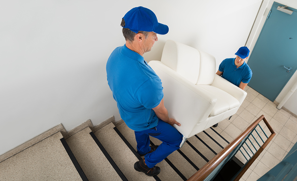 Two movers move a couch down a fight of stairs.