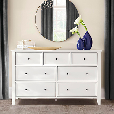 A large white dresser in a bedroom.