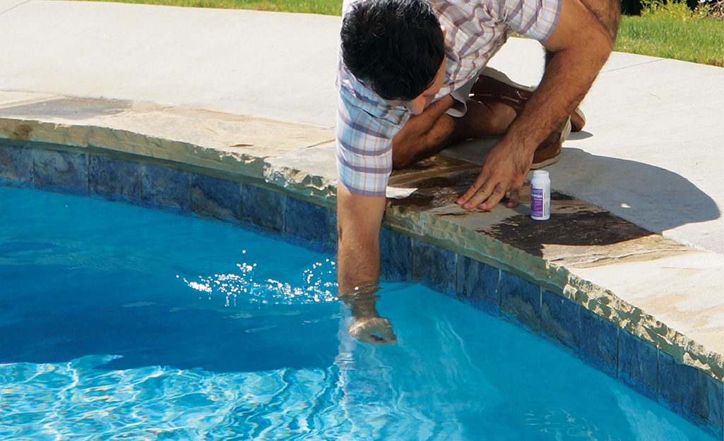 Man checks the chemicals in a pool