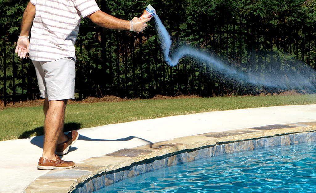 Person pours chemicals in a pool