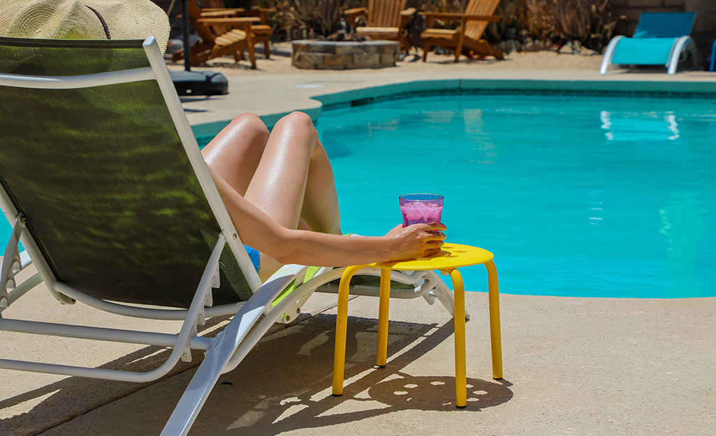 Woman sitting in patio chair by swimming pool
