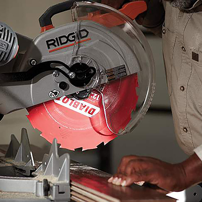 A power miter saw in position to cut a board.