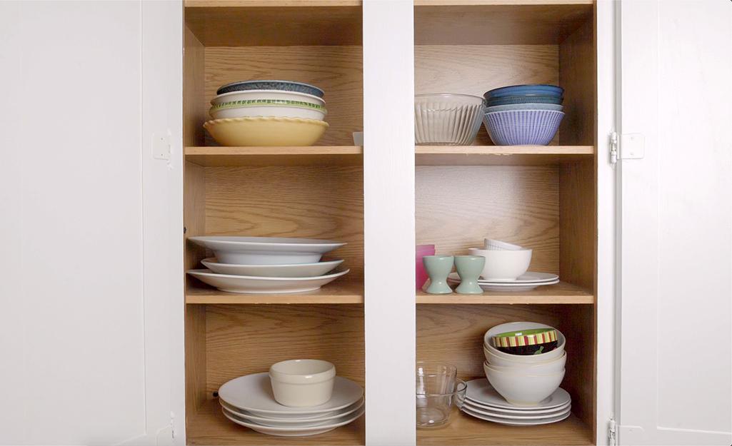 A kitchen cabinet housing unorganized dishes.
