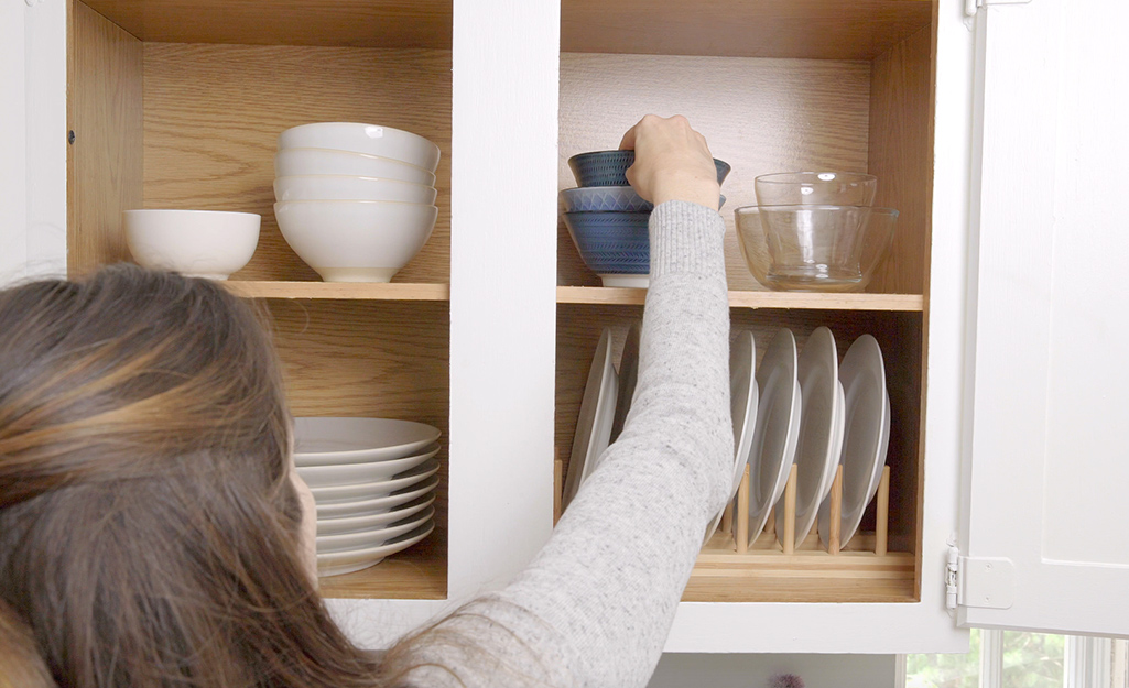 A woman sorts and stacks plates to organize them.
