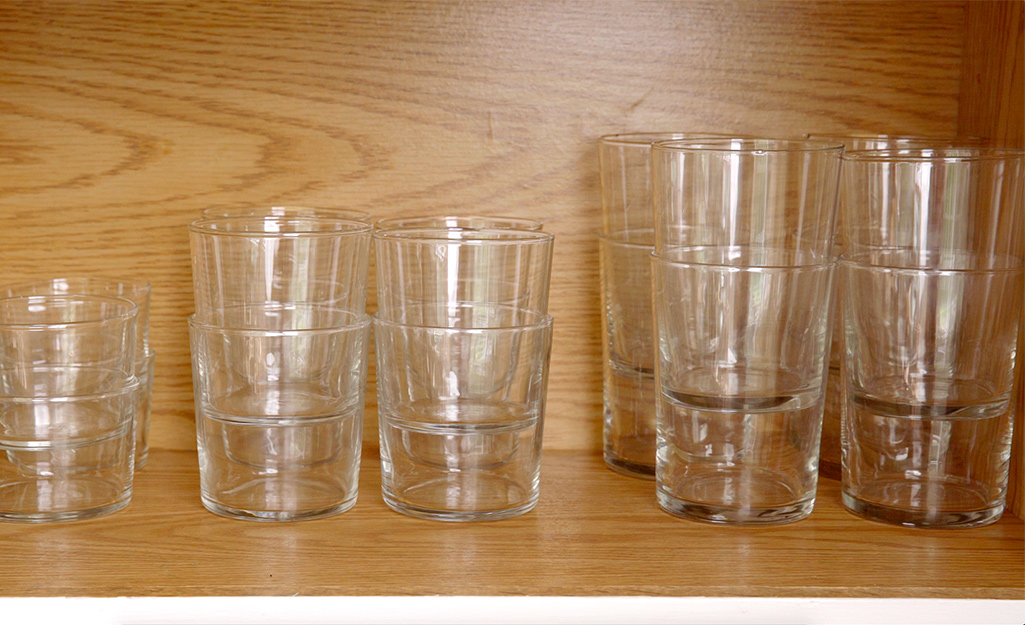 Glassware in a cabinet is stacked by size.