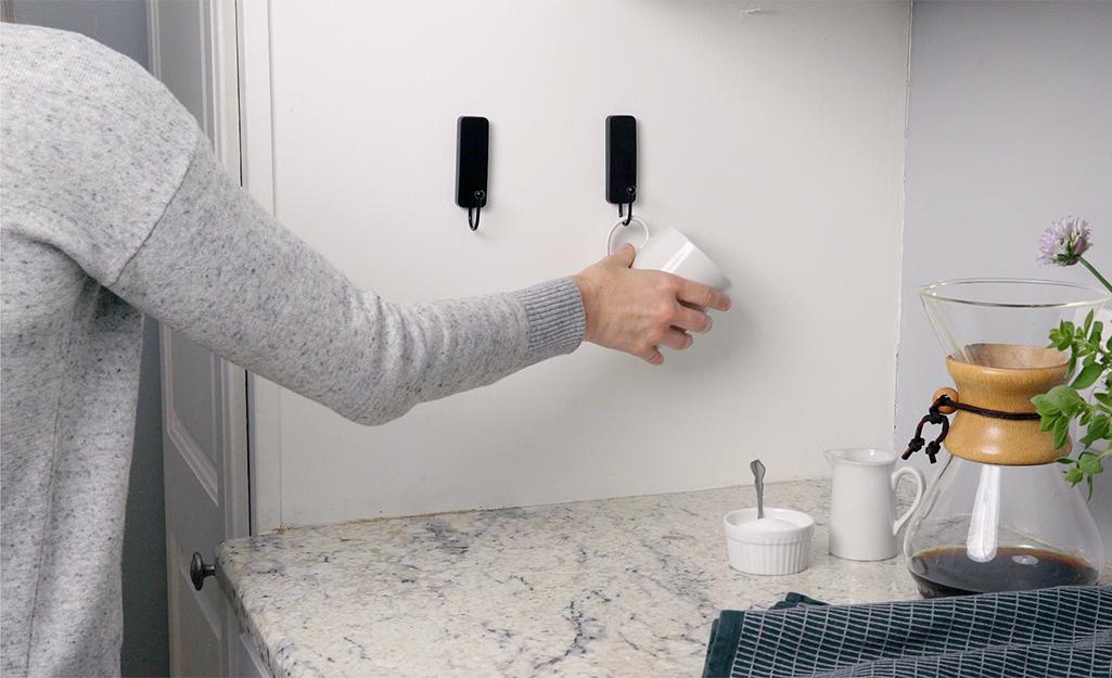 A woman uses wall hooks to hang coffee mugs near her coffee pot.