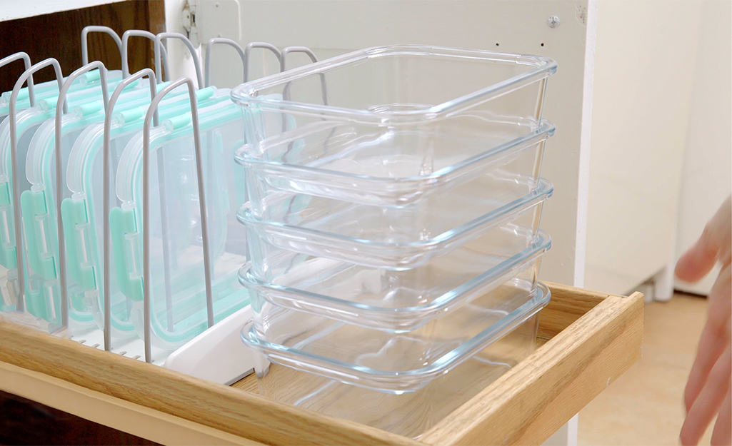 A pull-out cabinet features organized food storage containers.