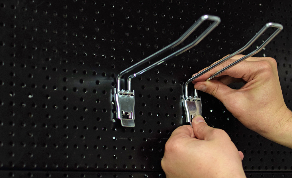 hands installing hooks on a pegboard