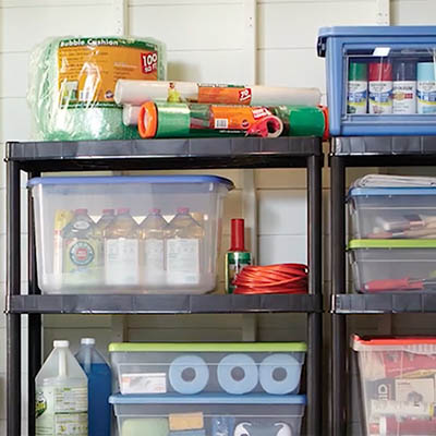 A garage organized with shelves, bins and more.