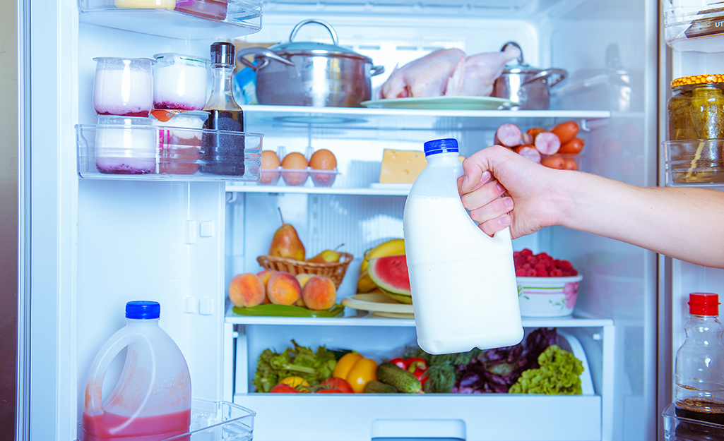 Person removing milk from the fridge.